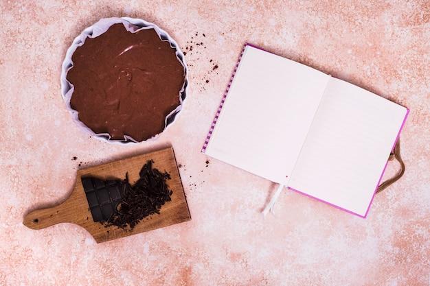 Ein offenes leeres weißes tagebuch mit kuchen und gebrochenem schokoriegel auf hackendem brett über dem strukturierten hintergrund