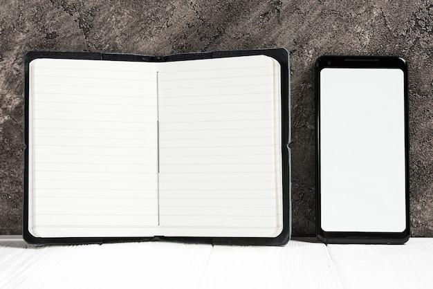 Ein offenes tagebuch und ein handy, die weißen bildschirm auf schreibtisch gegen wand zeigen