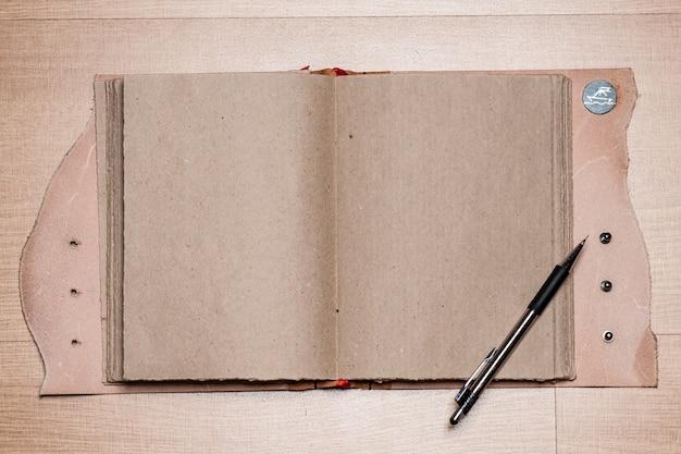 Ein offenes weinlese-sketchbook oder ein notizbuch mit bleistift auf altem holztisch.