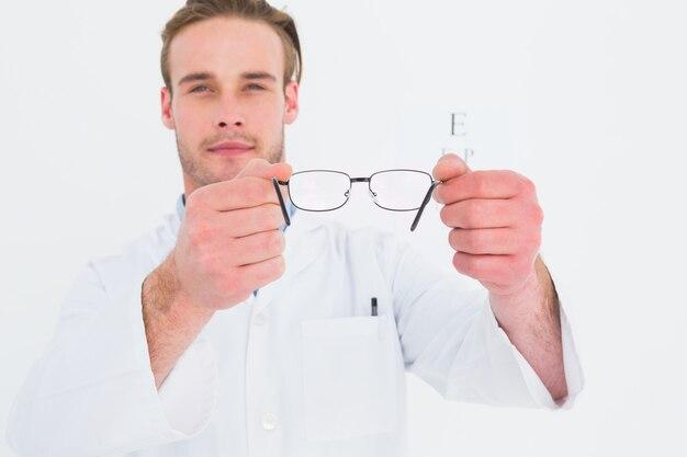 Ein optiker, der brillen neben einem sehtest zeigt