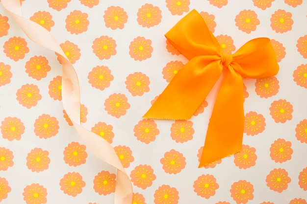 Ein orange bogen und ein gekräuseltes band auf blumengeschenkpapier