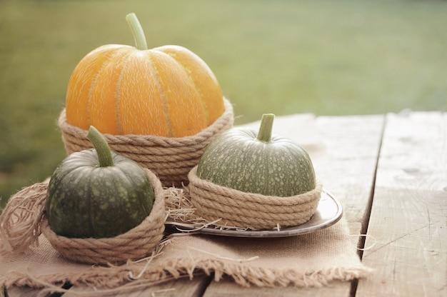 Ein orangefarbener kürbis und zwei grüne kürbisse auf dem holztisch verzierten sackleinen und seil. draußen.