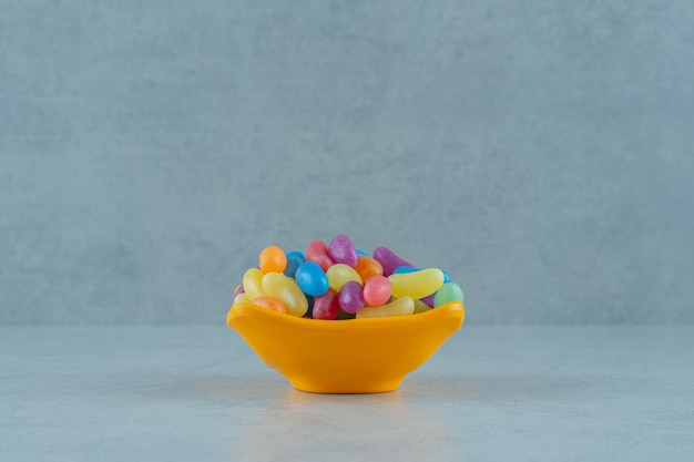 Ein orangefarbener teller mit bunten jelly bean bonbons auf weißer oberfläche