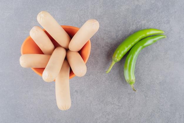 Ein orangefarbener teller mit gekochten würstchen mit chilischoten