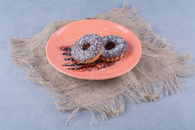 Ein orangefarbener teller mit köstlichen schokoladendonuts mit streuseln auf einem sack.
