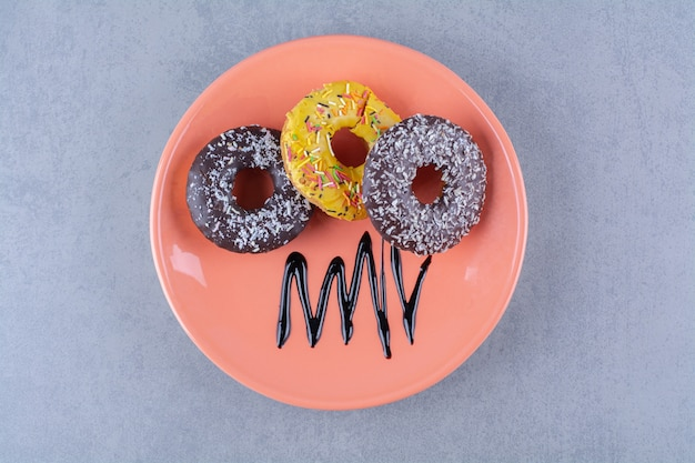 Ein orangefarbener teller mit leckeren schokoladenkrapfen mit streuseln.