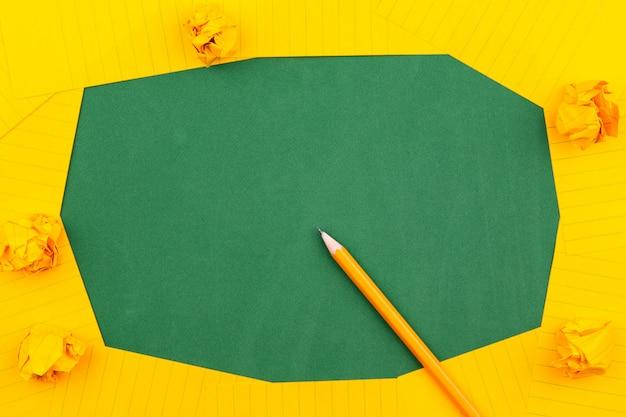 Ein orangefarbenes blatt papier liegt auf einer grünen schulbehörde, die einen rahmen für text bildet. in der nähe von bleistift und zerknitterten seiten. kopieren sie platz wohnung legen draufsicht konzept bildung.