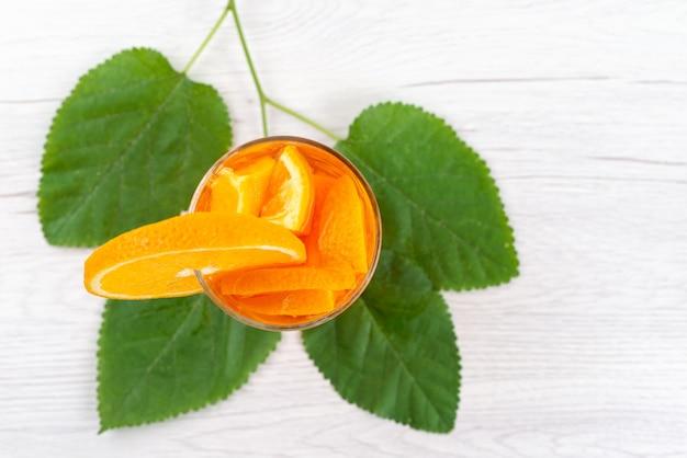 Ein orangencocktail von oben mit frischem orangenstück zusammen mit grünen blättern auf weißem cocktailgetränk fruchtkühlung