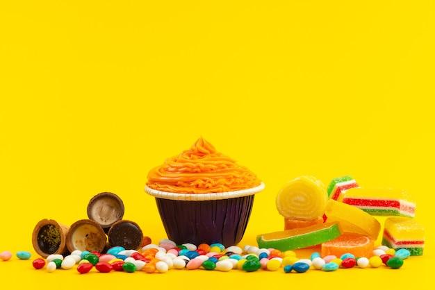 Ein orangenkuchen der vorderansicht mit bunten bonbons und marmeladen auf gelbem, keksfarbenem zucker süß