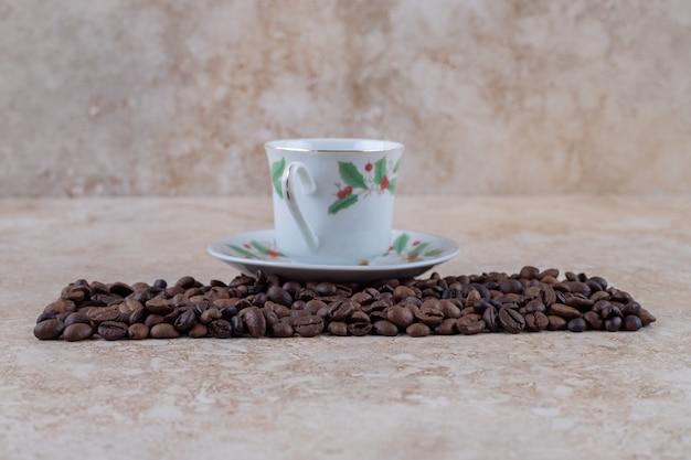 Ein ordentlicher kaffeebohnenhaufen und eine tasse kaffee auf einer untertasse