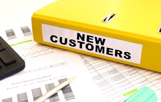 Ein ordner mit dokumenten mit der bezeichnung neue kunden liegt mit finanzdiagrammen auf dem schreibtisch