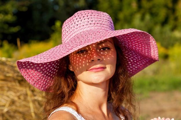 Ein outdoor-porträt einer schönen frau im rosa hut auf dem hintergrund eines weizenfeldes.
