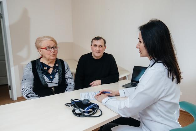 Ein paar ältere menschen bei einem persönlichen arzttermin in einem medizinischen zentrum. medizin und gesundheitswesen
