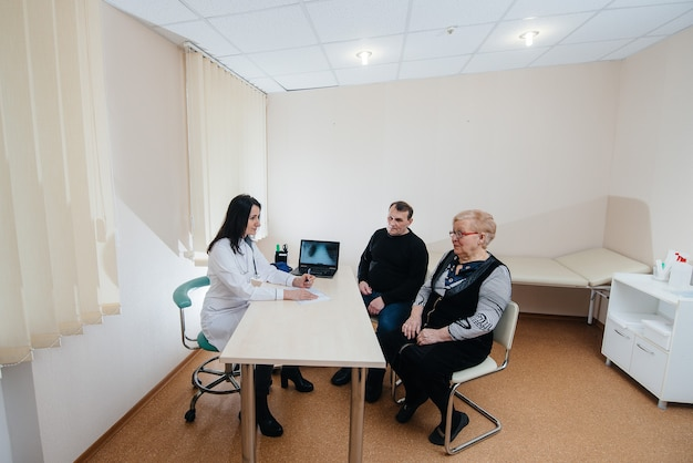 Ein paar ältere menschen bei einem persönlichen arzttermin in einem medizinischen zentrum. medizin und gesundheitswesen.