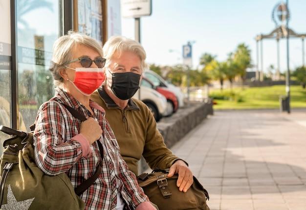 Ein paar ältere reisende sitzen auf der bank, während sie auf den bus warten und eine chirurgische maske tragen