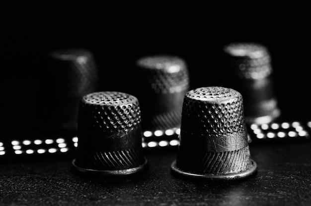 Ein paar alte fingerhüte auf einem schwarzen. brillantes armband. einfarbig.