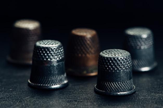 Ein paar alte fingerhüte auf einem schwarzen hintergrund.