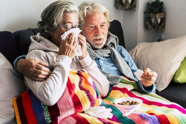 Ein paar alte senioren zu hause mit saisonaler winterkältekrankheit sitzen für immer zusammen auf dem sofa