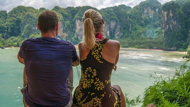 Ein paar am aussichtspunkt t hat tom sai beach bei railay in der nähe von ao nang, krabi, thailand.