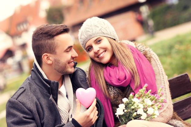 Ein paar am valentinstag im park mit blumen und herz