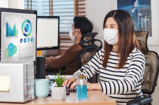 Ein paar asiatische kollegen, die die chirurgische maske tragen und mit dem computer im home office arbeiten
