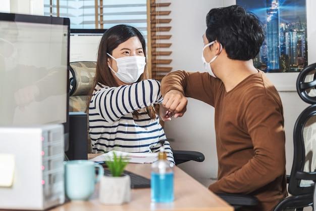 Ein paar asiatische kollegen, die die chirurgische maske und die ellbogen tragen, stoßen mit partnerschaft an