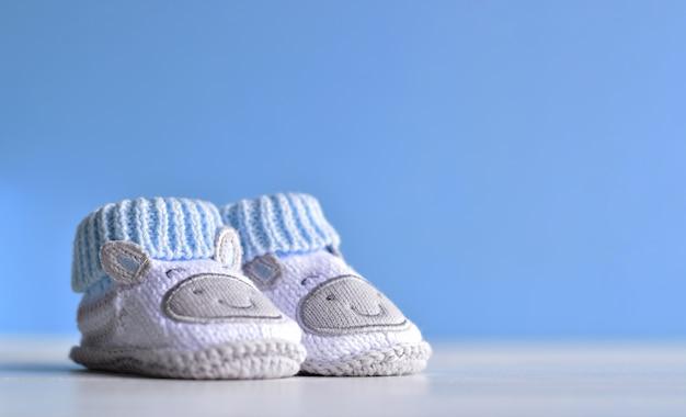 Ein paar babyschuhe auf weißem bretterboden und blauem gackground