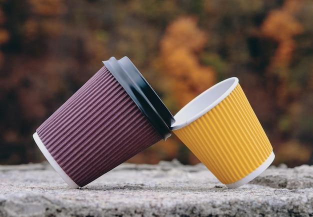 Ein paar braune und gelbe pappbecher zum mitnehmen, kaffee zum mitnehmen.