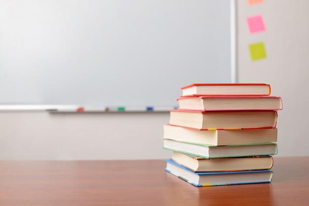 Ein paar bücher auf der schulbank vor einem whiteboard