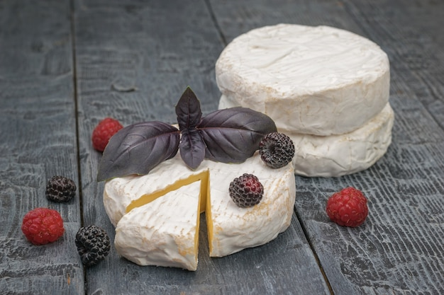 Ein paar camembert-käse, beeren und basilikum auf einem holztisch. ein produkt aus natürlicher milch.