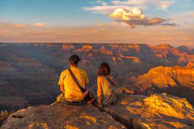 Ein paar, das bei sonnenuntergang am powell point des grand canyon sitzt. arizona, vertikales foto