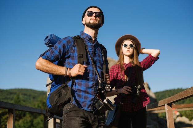 Ein paar, das durch die berge reist und hipster-kleidung mit rucksack, vintage-kamera und fernglas trägt