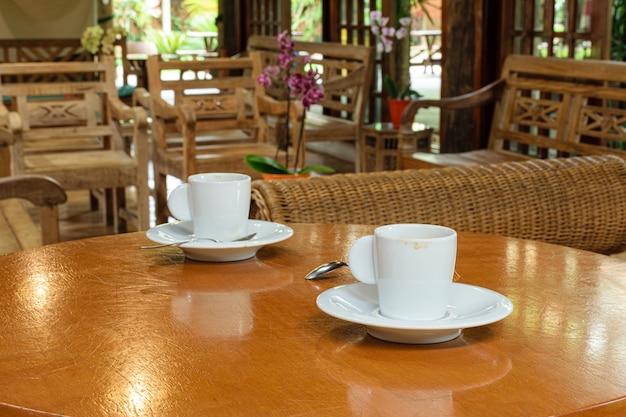 Ein paar einsame tassen kaffee auf dem tisch (seitenansicht).