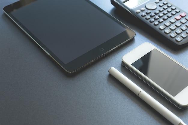 Ein paar elektronische geräte auf grauem hintergrund angezeigt. smartphone, pad und taschenrechner, alle digital außer einem stift. szene arbeitsplatz.