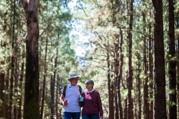 Ein paar erwachsener senioren mit rucksack, die zusammen mitten in einem hohen baumwald spazieren gehen - konzept von fernweh und alten menschen im aktiven alter bei freizeitaktivitäten im freien - alternativer urlaub