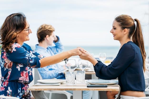 Ein paar frauen, die hände halten, während sie einander an einem restauranttisch lächelnd ansehen