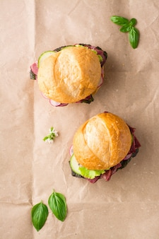 Ein paar frische burger mit pastrami, gurke, rettich und kräutern auf kraftpapier. amerikanisches fastfood.