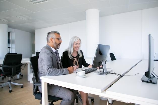 Ein paar fröhliche geschäftskollegen, die inhalte auf dem computermonitor ansehen, lächeln und lachen, während sie am arbeitsplatz sitzen. geschäftskommunikationskonzept