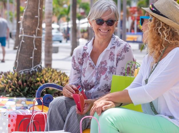 Ein paar glückliche, freundliche frauen, die nach dem einkauf im winterverkauf mit vielen einkaufstüten sitzen und kreditkarte verwenden. konsumkonzept