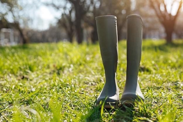 Ein paar grüne gummistiefel, die auf frischem jungem gras auf einem landschaftshintergrund des landes stehen