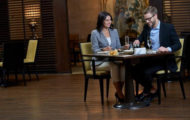 Ein paar gut gekleidete kunden sitzen an einem tisch mit sushi-gerichten, während der mann mit gabel und dame mit stäbchen isst eating