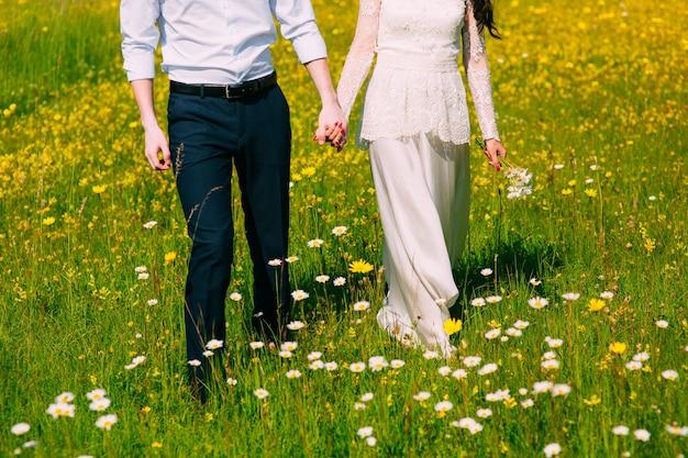 Ein paar hält hände auf einem feld mit gänseblümchen der jungvermählten