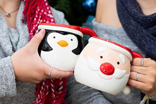 Ein paar hände von ein paar zwei frauen, die zu weihnachten tassen mit heißer schokolade halten