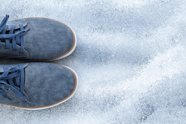 Ein paar herrenschuhe, blaue jeanssneaker und bequemes textilschuhwerk. beiläufige art und weise