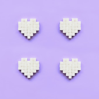 Ein paar herzen aus zuckerwürfeln liegen auf einem trendigen violetten pastellhintergrund