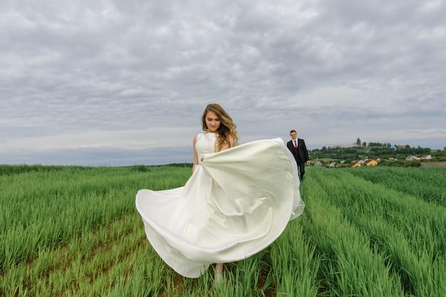 Ein paar in einer hochzeitskleidung steht auf einer grünen wiese in einem dorf bei sonnenuntergang, die braut und der bräutigam. die braut dreht sich in ihrem kleid. der bräutigam bewundert sie.