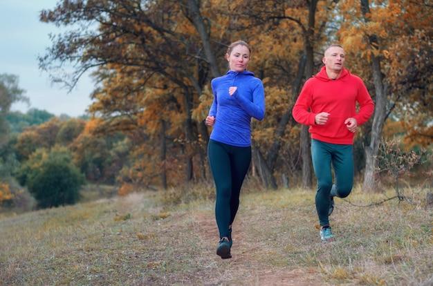Ein paar jogger in schwarzen leggins und einer farbigen jacke rennen schnell den weg entlang in einem farbenfrohen herbstlichen waldhügel.