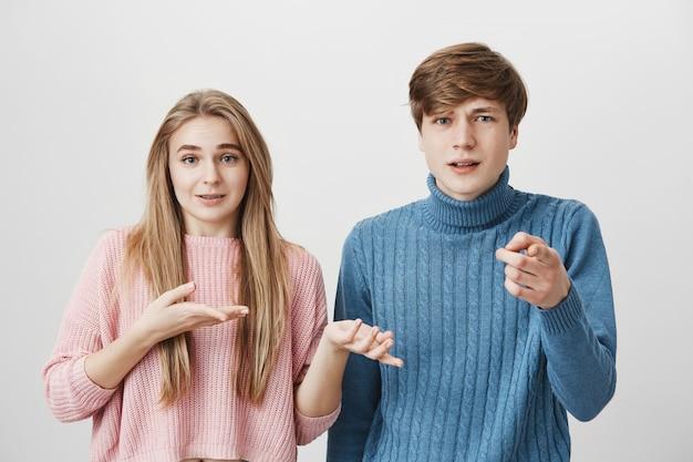 Ein paar jugendliche, die mit den zeigefingern zeigen. junger blonder mann, der auf kamera mit unzufriedenem gesichtsausdruck zeigt