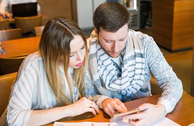 Ein paar junge designer, die mit zwei mitarbeitern arbeiten, die über ein lustiges projekt diskutieren, ein kleines team von geschäftsleuten