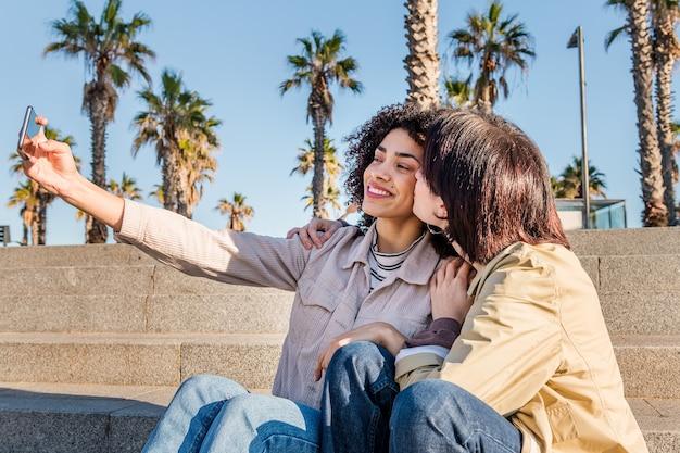 Ein paar junge frauen, die ein selfie mit einem telefon machen
